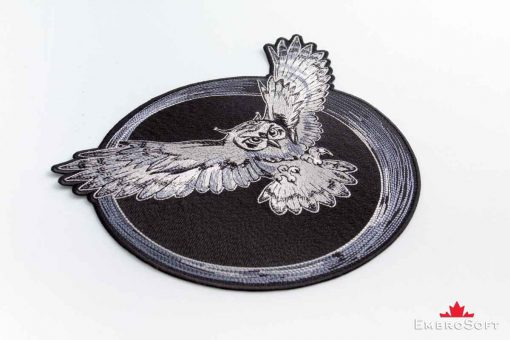 The embroidered patch Flying Owl lying ob surface