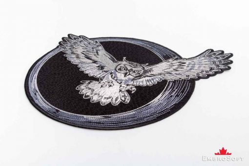 The embroidered patch Flying Owl on white surface