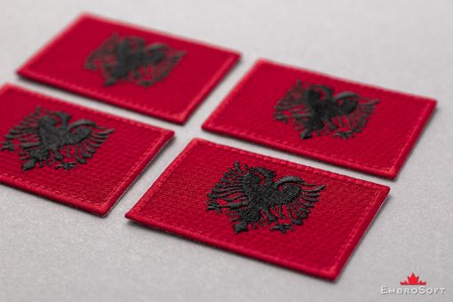 Flag Embroidered Patch of Albania Lying On Surface Photo