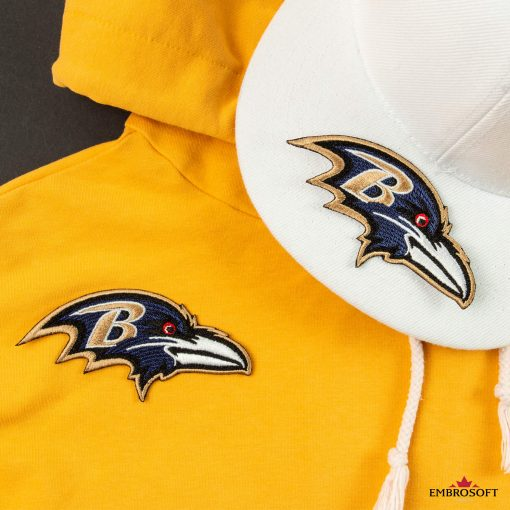 Baltimore Ravens embroidered patch with NFL team emblem on a yellow hoody and white cap